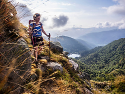 Women hiking downwards of mountain with forest and lake Schiessrothried in backgrounds at Lac Blanc, France