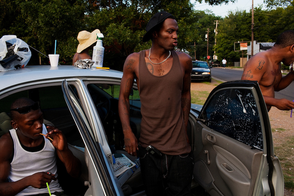 "Eddie ""Prime-Time"" Taylor rolls a blunt while Roger ""Winky"" Williams (center) washes windows on a car he is preparing to tint in the Baptist Town neighborhood of Greenwood, Mississippi on July 3, 2010."