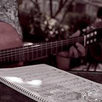 Man playing guitar from sheet music