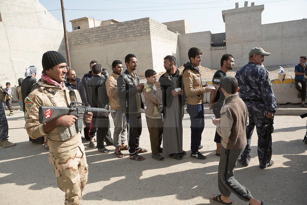 Licensed to London News Pictures. 11/11/2016. Mosul, Iraq. A soldier, of the Iraqi Army's 9th Armoured Division, stands guard as residents of Mosul's Al Intisar District queue for food being handed out by volunteers.<br /> <br /> The battle to retake Mosul, which fell June 2014, started on the 16th of October 2016 with Iraqi Security Forces eventually reaching the city on the 1st of November. Since then elements of the Iraq Army and Police have succeeded in pushing into the city and retaking several neighbourhoods allowing civilians living there to be evacuated - though many more remain trapped within Mosul.  Photo credit: Matt Cetti-Roberts/LNP