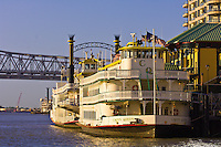 Riverboats docked along the Mississippi River with the Crescent City Connection Bridge in back, New Orleans, Louisiana, USA