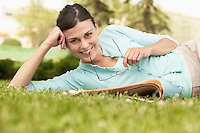 Woman lying on grass with newspaper holding glasses portrait.