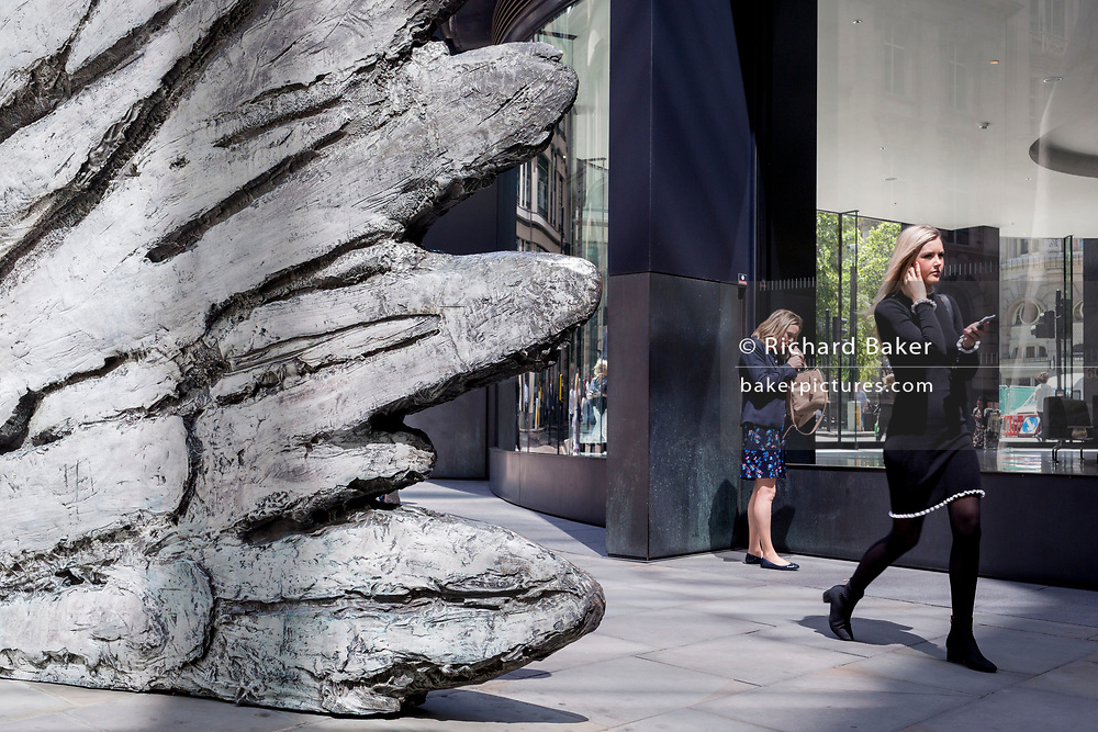 A lady lights a cigarette as a younger, healthier woman walks past the sculpture entitled 'City Wing' on Threadneedle Street in the City of London, the capital's financial district, on 17th June 2019, in London, England. This ten-metre-tall bronze sculpture is by President of the Royal Academy of Arts, Christopher Le Brun, commissioned by Hammerson in 2009. 'The City Wing' and has been cast by Morris Singer Art Founders, reputedly the oldest fine art foundry in the world.