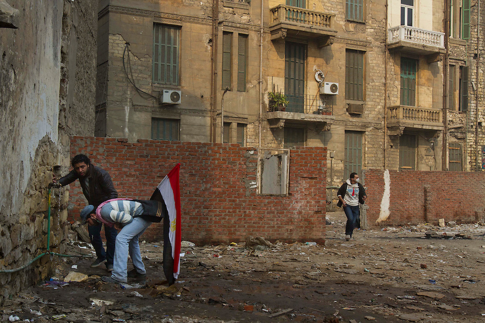 Egyptian men run away from tear gas next to Tahrir Square on November 22, 2011 photo by: Maya Levin