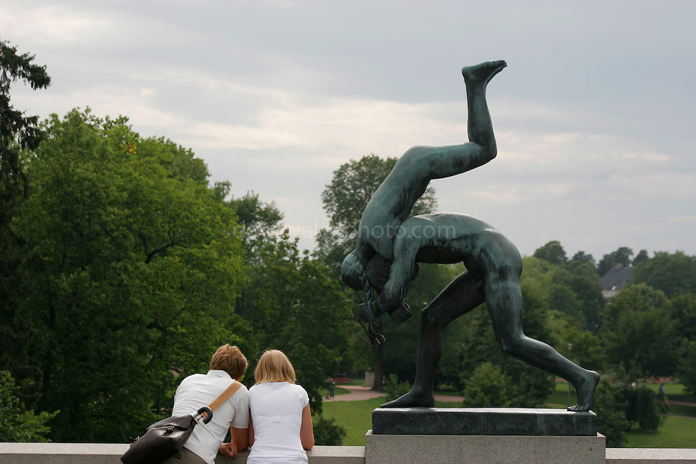 Two lovers in conversation beside one of Gustave Vigeland's sculptures in Vigeland Park, Oslo. The statue depicts a man throwing a woman over his shoulder, violently...