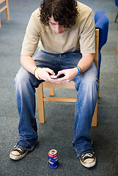 Teenage boy; taking a break; texting on his mobile phone in the school common room,