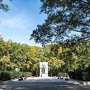 A large statue of Theodore Roosevelt set amongst the trees at the Theodore Roosevelt Memorial in Arlington, VA.