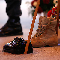 PUNTA GORDA, FL -- March 13, 2008 -- The boots and dress shoes of former Marine Eric Hall sit as a Marine stands at attention during his memorial service at the Faith Lutheran Church in Punta Gorda, Fla., on Thursday, March 13, 2008.  Hall went missing on Feb. 3 after having a flashback to his time in Iraq, and was found dead weeks later by the Vietnam veteran volunteers in a culvert.