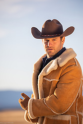 rugged good looking cowboy in a shearling coat on a ranch at sunset