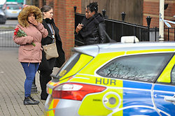 © Licensed to London News Pictures. 20/02/2018. LONDON, UK. Wellwishers arrive with floral tributes. Police officers and a forensics team attend the scene in Halliday Square, Southall, West London, where a 26 year old man was fatally stabbed on the afternoon of 19 February.  A 39 year old man was arrested at the scene and is in custody.  Investigations are ongoing.  Photo credit: Stephen Chung/LNP