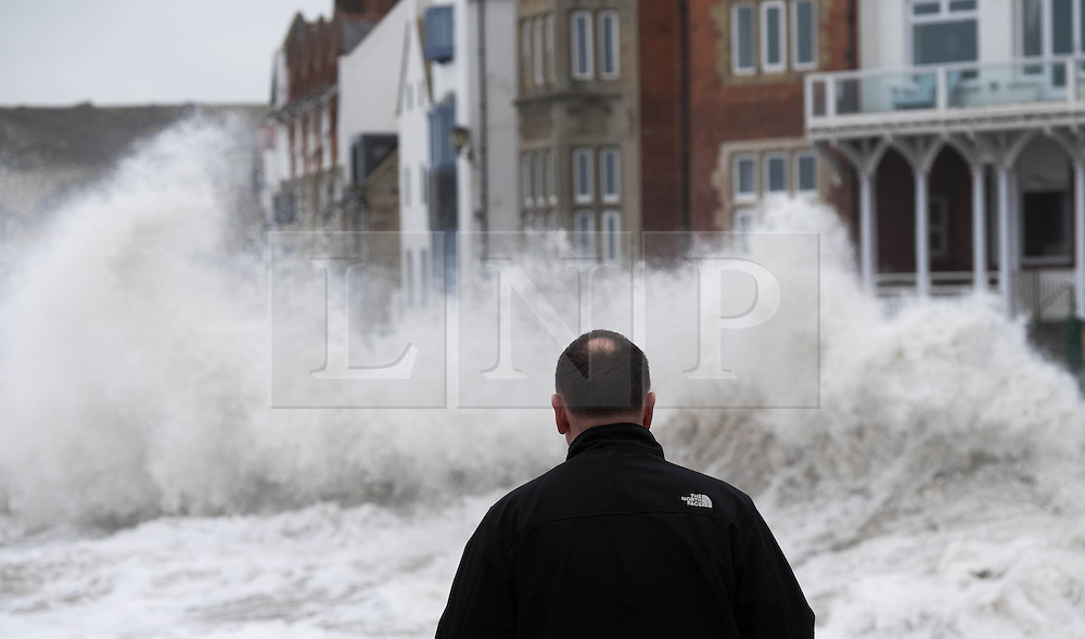 © Licensed to London News Pictures. <br /> 21/03/2015. <br /> <br /> Sandsend, North Yorkshire.<br /> <br /> A man looks on as a huge wave crashes against the sea wall at Sandsend in North Yorkshire. The exceptionally high Spring tides were created by the moon's 18-year cycle.<br /> <br /> Photo credit : Ian Forsyth/LNP