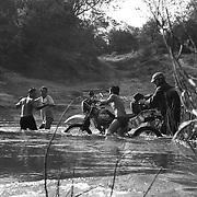 """Steve Christiansen (R) and Digby Greenhalgh (L) get a little help from local villagers as they cross the Senphen tributary of the Bangphai River, outside the """"bomb village"""" of Ban Senphen. The village is located in the Ban Phanhop valley, one of the """"chokes"""", or narrow corridors along the Ho Chi Minh Trail in Laos that were heavily bombed by American forces during the Vietnam War."""