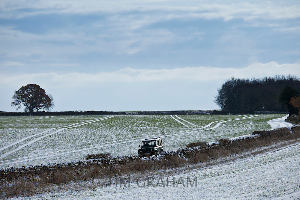 Land Rover driving along frosty track in wintry landscape in The Cotswolds, Oxfordshire, UK