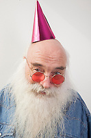 Portrait of senior man wearing red glasses and party hat over gray background