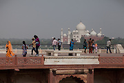 Visitors are looking at the Taj Mahal from the high walls of the Agra Fort, opposite the heavily polluted and dry Yamuna River, in Agra.
