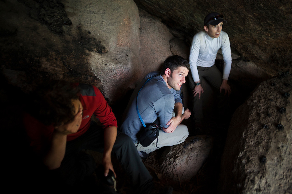 Marco Binotti (l-r), Obadiah Reid, and David Coffey take shelter from a storm inside a small cave in the Lost Creek Wilderness, Colorado.