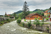 Stream babbling through the old historic town of Appenzell Switzerland with old world buildings nestled in bright green countrside