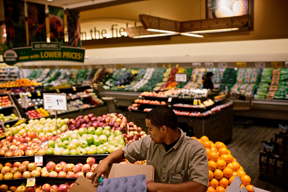 Elio Perdomo, restocks apples in the produce section at a Safeway grocery store in Silver Sping, MD. Perdomo, a student at Montgomery College, tries to take classes in the morning and works up to 16 hours a week at the supermarket.