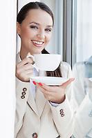 Portrait of happy businesswoman having coffee in office