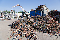 Pile of copper tube in foreground before baling with hydraulic grab machine in the background lifting aluminium up ready to be put in baler at metal recycling centre,