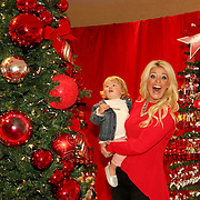 Country music singer Lauren Alaina holds 2 year old Julia Roth who is visiting from Indiana with her mother Kristen. Macy's Great Tree Lighting, on Saturday, November 2, 2013 at Macy's State Street in Chicago. Macy's launched its annual Believe Campaign in support of Make-A-Wish.  (Jose More/AP Images for Macy's)