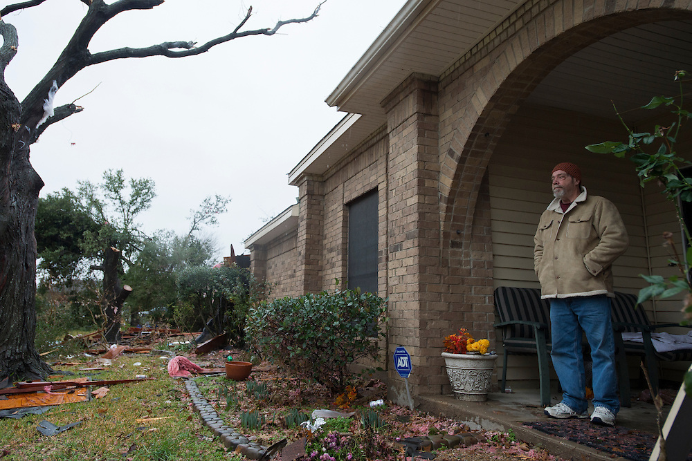 Paul Gorman stands on his porch looking at the damage to his neighborhood where homes were hit by a tornado the previous evening in Garland, Texas on December 27, 2015. (Cooper Neill for The New York Times)