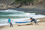 Two men push a boat through the sand at Red Beach in the Urca neighborhood of Rio de Janeiro, Brazil.