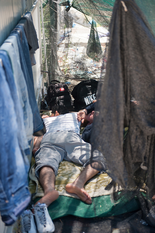 Refugees sleep in a makeshift tent in Moria camp.