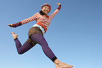 Young woman jumping in striped outfit