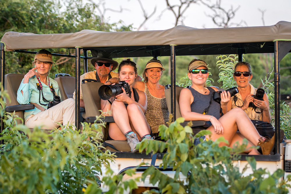 A group of tourists in a safari caravan all hold up their cameras and pose. Chobe National Park - Botswana
