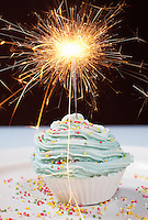 Single cupcake with lit sparkler