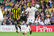 Watford midfielder Roberto Pereyra (37) chips ball forward with Manchester United Midfielder Paul Pogba during the Premier League match between Watford and Manchester United at Vicarage Road, Watford, England on 15 September 2018.