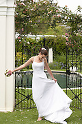 Mid adult bride standing in garden holding bouquet and dress laughing