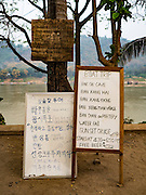 "11 MARCH 2016 - LUANG PRABANG, LAOS:  Sign boards for tourists in English and Korean in Luang Prabang. The Mekong River is in the background. Luang Prabang was named a UNESCO World Heritage Site in 1995. The move saved the city's colonial architecture but the explosion of mass tourism has taken a toll on the city's soul. According to one recent study, a small plot of land that sold for $8,000 three years ago now goes for $120,000. Many longtime residents are selling their homes and moving to small developments around the city. The old homes are then converted to guesthouses, restaurants and spas. The city is famous for the morning ""tak bat,"" or monks' morning alms rounds. Every morning hundreds of Buddhist monks come out before dawn and walk in a silent procession through the city accepting alms from residents. Now, most of the people presenting alms to the monks are tourists, since so many Lao people have moved outside of the city center. About 50,000 people are thought to live in the Luang Prabang area, the city received more than 530,000 tourists in 2014.      PHOTO BY JACK KURTZ"
