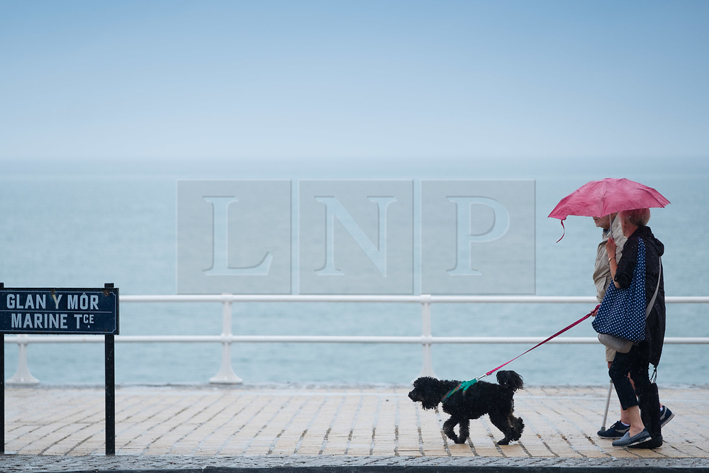 ©Licenced to London News Pictures. Aberystwyth, UK, 17/07/2018. After many weeks of almost constant sunshine and exceptionally dry weather, the rains have returned with people seen sheltering from the downpour under their umbrellas as they walk their dog along the promenade in Aberystwyth on the west Wales coast. Photo credit: Keith Morris LNP