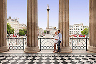 Couple on the portico of London's National Gallery with Trafalgar Square and Nelson's Column in the background. Photographed for Visit Britain as part of their 2013 culture campaign. THIS IMAGE IS COPYRIGHT VISIT BRITAIN.