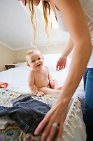 An infant boy sits on a bed as his mother prepares to change his clothes.