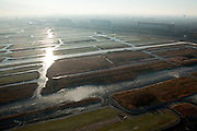 Nederland, Noord-Holland, Zaandam, 10-01-2009; Polder Oostzaan met het Oostzanerveld, vormt onderdeel van het Nationaal Landschap Waterland (Laag Holland); veenweidegebied, ontstaat door afgraven van turf; (nog) in gebruik voor veeteelt door 'waterboeren', bedreigd gebied, aan de horizon autosnelweg A9 en de flats en hoogbouw  van Zaandam;.the landscape is the result of diging up the peat in the past; still in use by cattle farmers (cows, dairy-catle); landscape under threat, motorway A8 and high rise buildings Zaandam at the horizon;.winterlandschap, winter landscape; . .luchtfoto (toeslag); aerial photo (additional fee required); .foto Siebe Swart / photo Siebe Swart