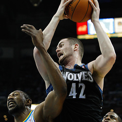 February 7, 2011; New Orleans, LA, USA; Minnesota Timberwolves power forward Kevin Love (42) grabs a rebound over New Orleans Hornets center D.J. Mbenga (28) and point guard Chris Paul (3) during the third quarter at the New Orleans Arena. The Timberwolves defeated the Hornets 104-92.  Mandatory Credit: Derick E. Hingle