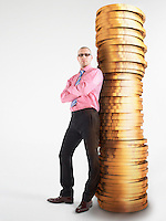 Man in glasses leaning against pile of coins digital composite