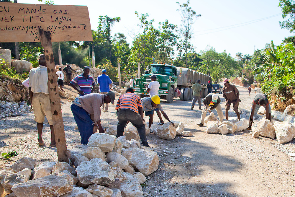 Angry farmers block only OAS and government vehicles at a road block. Hundreds of farmers are waiting to be compensated by the government for gardens lost due to road widening. The Inter-American Development Bank is funding this road project in the south of Haiti, aiming to cut travel time and transportation costs, and to improve living conditions in the southern provinces. This 50-mile stretch of road connects the small cities of Les Cayes and Jeremie and many rural villages in between. A Brazilian company, OAS, is doing the construction. The road is far from complete, but is already transforming commerce and daily life in the area. Travel time has been cut in half; fewer trucks are breaking down, so less food is spoiled; and farmers are planting more crops in anticipation of more dependable farm-to-market transportation.