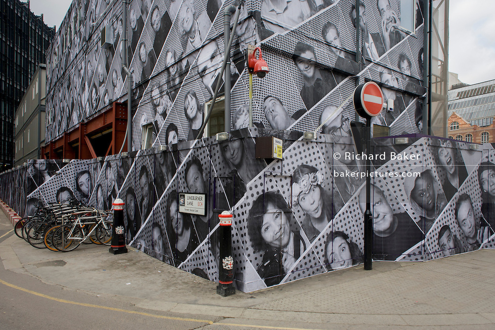 A construction hoarding featuring dozens of London faces in the City.