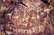 """This panel, called """"Pantheon of Sun Gods"""" by archeologists, is one of more than 2,000 Petroglyphs at Tamghali created between the Bronze Age and the Renaissance.  Petroglyphson five large rock faces can be viewed as one from a nearby ceremonial site as the setting sun illuminates them.  This detail describes the Kazakh faith called Tengri.  The one horizontal person on the bottom left represents, Mother Earth from whom all life issues.  The line of dancing figures represents tyhe physical dimension of our lives on earth.  The sun god figures represent the dimension of the Great Spirit and our ancestors.  These three levels of existence are not separate, but exist concurrently and in unity.  Tamghali is on an ancient north-south route in the Chu-ili mountains of southeastern Kazakhstan."""