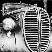 A view of the front grille of a vintage, antique Ford fire engine that is slowly rusting away in the Old Car City junkyard in Georgia.