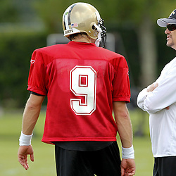 July 29, 2011; Metairie, LA, USA; New Orleans Saints general manager Mickey Loomis talks with quarterback Drew Brees (9) during the first day of training camp at the New Orleans Saints practice facility. Mandatory Credit: Derick E. Hingle