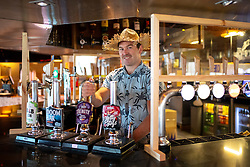 © Licensed to London News Pictures. 04/07/2020. Perranporth, UK. Tommy Job - manager of the Watering Hole, the UK's only bar on the beach - pours a pint of beer next to a protective sheet, shortly after opening time. Today marks a lift in COVID-19 restrictions, as pubs are allowed to open, whilst customers must still follow social distancing guidelines. Tens of thousands of tourists are due to arrive in Cornwall over this weekend, as overnight stays within England are also allowed. Photo credit : Tom Nicholson/LNP
