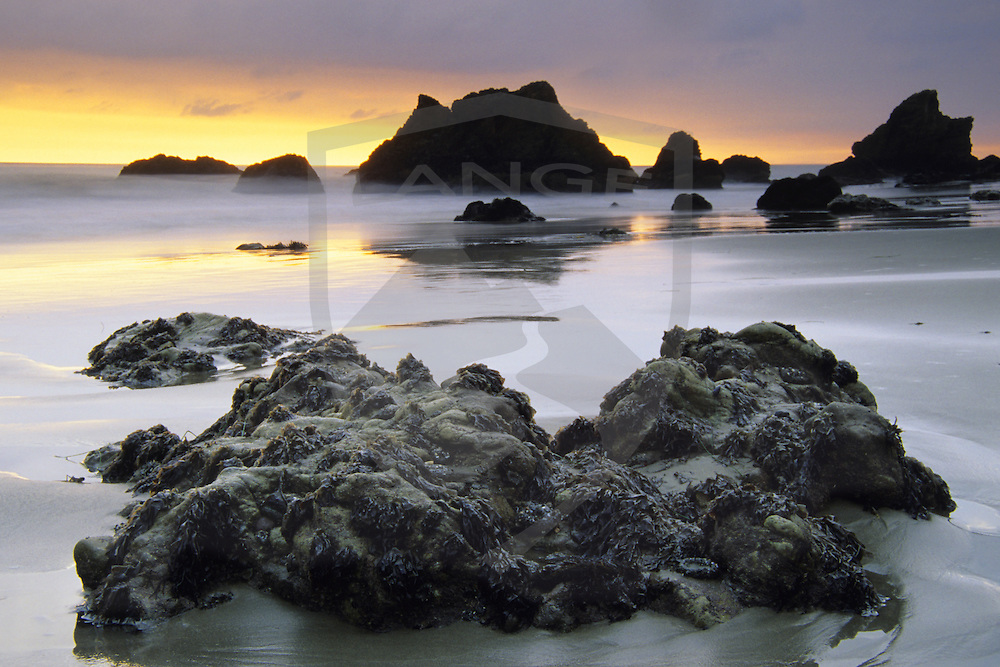 ocean landscape beach with boulder and sunset light on the horizon at el matador beach in malibu southern california.