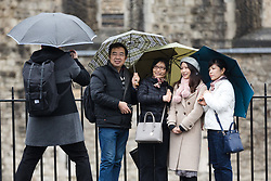 © Licensed to London News Pictures. 08/02/2019. London, UK.  Tourists take a photograph near the Tower of London during wet and windy weather. Storm Erik is the first named storm of 2019 with gale force winds and wet weather affecting most of the UK today. Photo credit: Vickie Flores/LNP