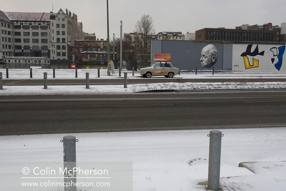 A Traband car being used as advertising standing on a snow-covered section of the route of the former Berlin Wall at the East Side Gallery in former East Berlin. The route of the Wall, which stood from 1962-1989, has been developed into the 'Mauerweg,' a thoroughfare which traces most of the route of the Wall which encircled the city and divided it into East and West Berlin during the Cold War. In the years following the 1989 civil uprising in the German Democratic Republic, most of the Wall was removed as part of the reunification strategy which united the pro-Soviet DDR and the Federal Republic of (West) Germany.