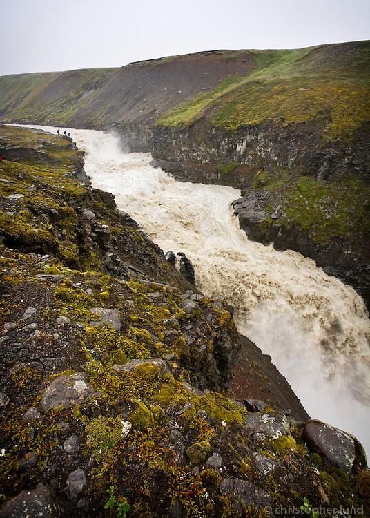 Hikers by river Kringils&aacute; in &Ouml;r&aelig;fi, Highlands of Iceland. Kringils&aacute; is a glacier river that will largely disappear due to the H&aacute;lsl&oacute;n resovoir that is being made for K&aacute;rahnj&uacute;kar Power Plant.<br /> <br /> Fl&uacute;&eth;ir &iacute; Kringils&aacute;. G&ouml;nguh&oacute;pur &aacute; vegum Augnabliks vir&eth;ir fyrir s&eacute;r &oacute;tr&uacute;legt gili&eth; og kraftinn &iacute; &aacute;nni.